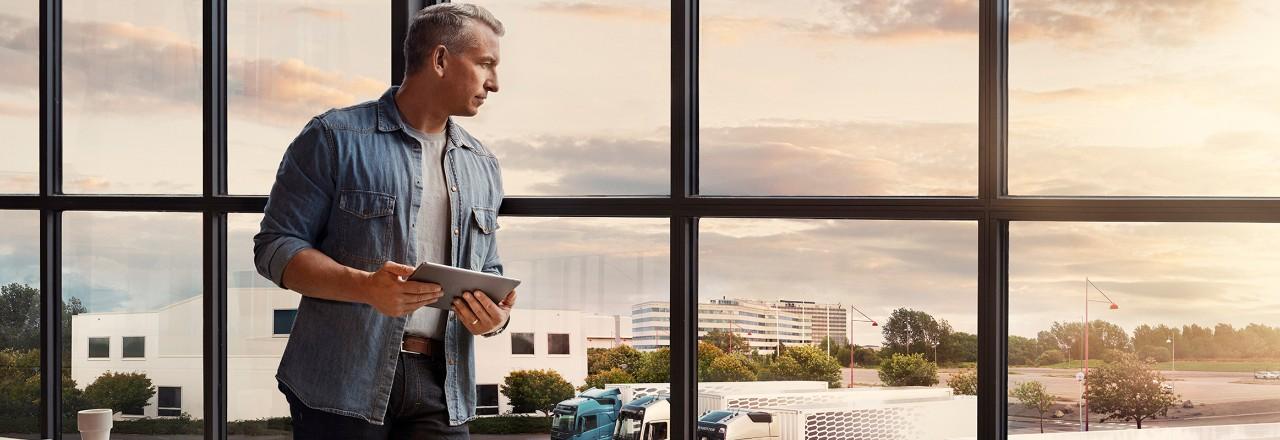 Mies seisoo tabletti kädessään ikkunan ääressä ja katsoo kuorma-autojaan